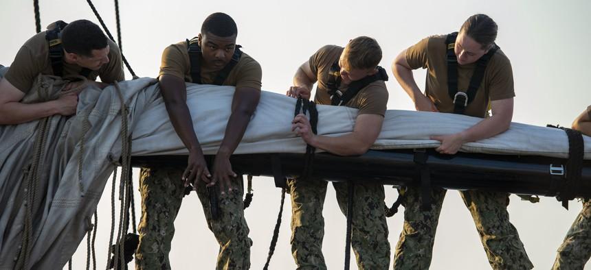 Sailors furl the mizzen topsail aboard USS Constitution in Boston, July 27, 2021.