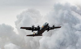 An Air National Guard C-130 flies over the plumes of smoke after dropping retardant on the Beckwourth Complex Fire, July 9, 2021 near Frenchman Lake in N. California.