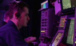 As part of Large Scale Exercise 2021, U.S. Navy Operations Specialist 3rd Class Jack Azzopardi tracks surface vessels in the combat information center aboard the San Antonio-class amphibious transport dock Arlington on Aug. 8, 2021.