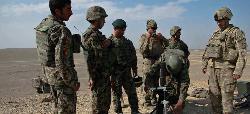 U.S. Army Staff Sgt. Lazarus Gonzalez with the 4th Infantry Division observes an Afghan National Army soldier as he adjusts his aim during field artillery training at Shinwar, Nangarhar province, Afghanistan, in 2012.
