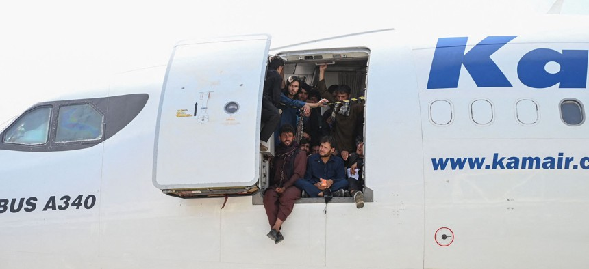 Afghan people climb up on a plane and sit by the door as they wait at the Kabul airport in Afghanistan, August 16, 2021.