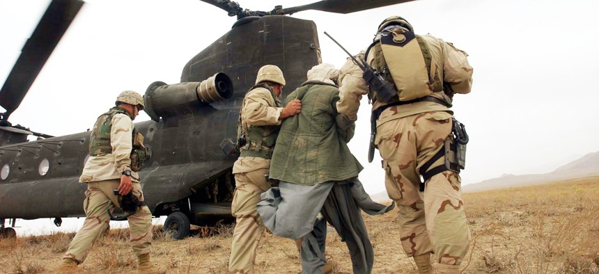 Afghan detainees are walked to a Chinook helicopter for transport by special operation forces after a joint village raid between U.S. Special Forces and the Afghan National Army, April 2, 2004, in southeast Afghanistan.