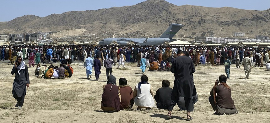 Hundreds of people gather near a U.S. Air Force C-17 transport plane at a perimeter at the international airport in Kabul, Afghanistan, on Aug. 16, 2021.