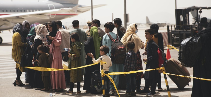 Civilians prepare to board a plane during an evacuation at Hamid Karzai International Airport, Kabul, Afghanistan, Aug. 18.