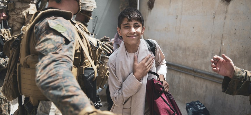 A boy is processed through an evacuee control checkpoint during an evacuation at Hamid Karzai International Airport, Kabul, Afghanistan, Aug. 18.