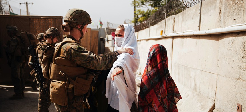 A U.S. Marine checks two civilians during processing through an Evacuee Control Checkpoint during an evacuation at Hamid Karzai International Airport, in Kabul, Afghanistan, on Aug. 18, 2021.