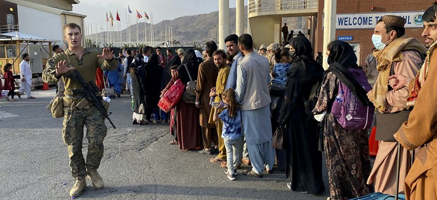 Afghan people queue up to board a U.S. military aircraft to leave Afghanistan, at the military airport in Kabul on August 19, 2021.