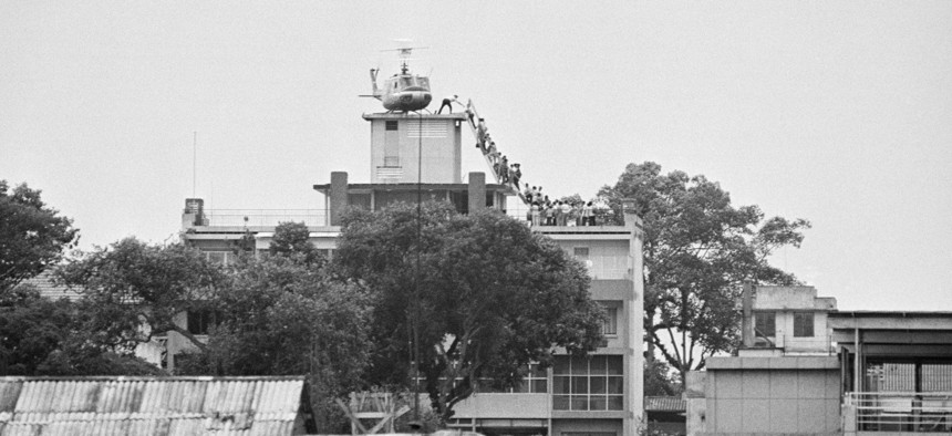 A CIA employee helps Vietnamese evacuees onto an Air America helicopter from the top of 22 Gia Long Street, a half mile from the U.S. Embassy.
