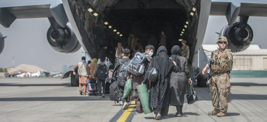 Families board a U.S. Air Force Boeing C-17 Globemaster III during an evacuation at Hamid Karzai International Airport, Kabul, Afghanistan, Aug. 23.
