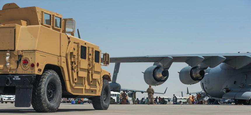 Evacuees from Kabul, Afghanistan, wait under the wing of C-17 Globemaster lll at an undisclosed location after arriving on Aug. 20, 2021.
