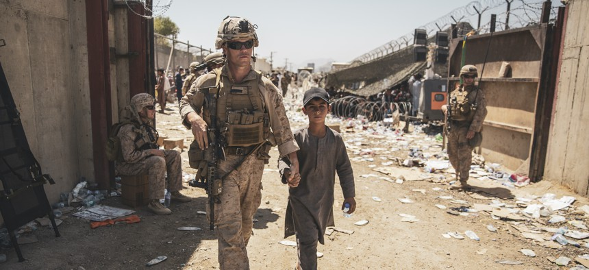 A U.S. Marine with the Special Purpose Marine Air-Ground Task Force-Crisis Response-Central Command escorts a child to his family during an evacuation at Hamid Karzai International Airport, Kabul, Afghanistan, Aug. 24.