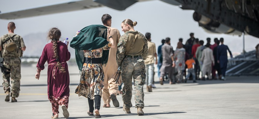 A Marine with the 24th Marine Expeditionary Unit walks with the children during an evacuation at Hamid Karzai International Airport, Kabul, Afghanistan, Aug. 24.