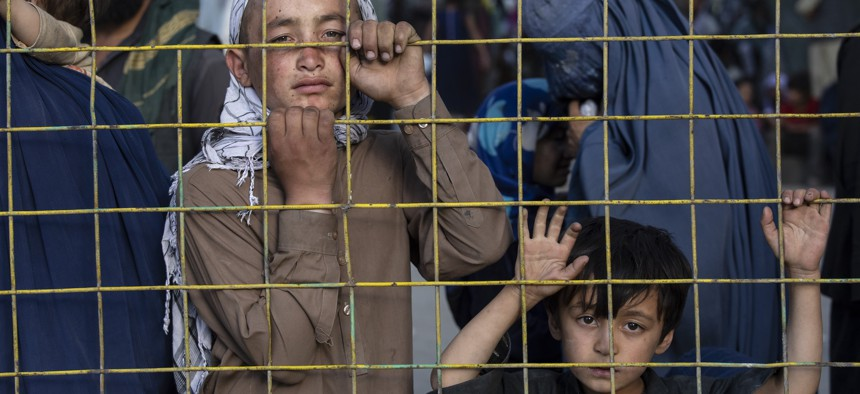 Displaced Afghans look through a fence at a makeshift IDP camp on August 12, 2021 in Kabul, Afghanistan.