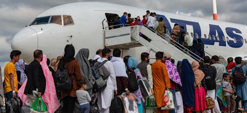 Evacuees board an Atlas Air aircraft for a departure flight from Ramstein Air Base, Germany, on their way to the United States as part of Operations Allies Refuge, Aug. 24, 2021.