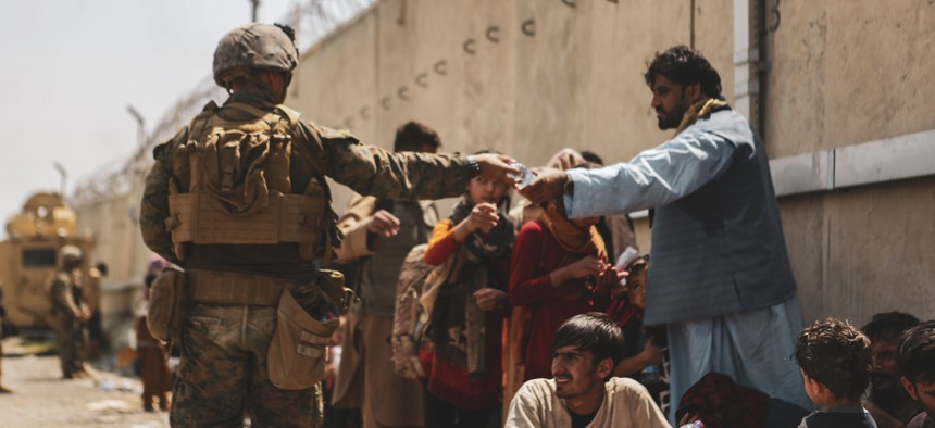 A Marine with the 24th Marine Expeditionary unit (MEU) passes out water to evacuees during an evacuation at Hamid Karzai International Airport, Kabul, Afghanistan, Aug. 22.
