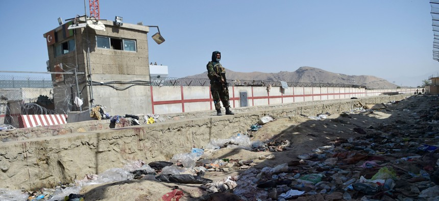 A Taliban fighter stands guard at the site of the August 26 suicide bomb attack that killed scores of people, including 13 U.S. troops, at Kabul airport on August 27, 2021.