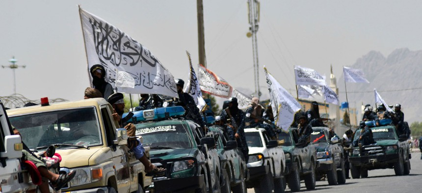 Taliban fighters atop vehicles with Taliban flags parade along a road to celebrate the U.S. pulled all troops out of Afghanistan, in Kandahar, on September 1, 2021.