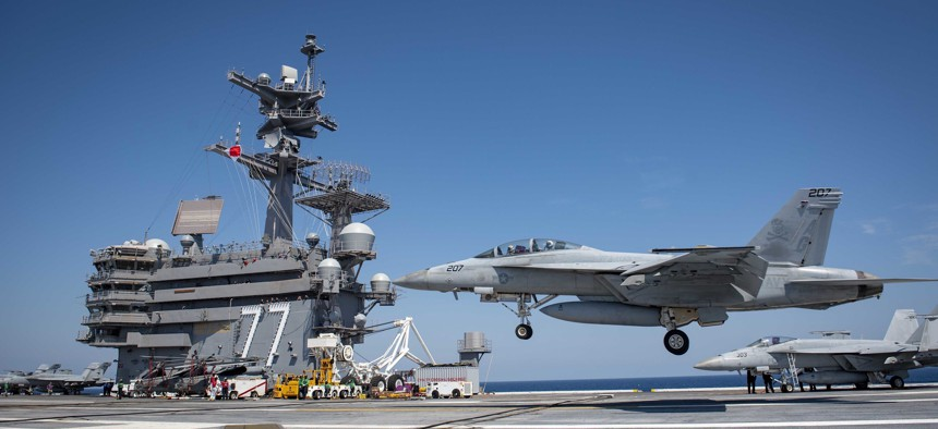 """An F/A-18F Super Hornet assigned to the """"Jolly Rogers"""" of Strike Fighter Squadron 103 performs a touch-and-go landing aboard the aircraft carrier USS George H. W. Bush during flight deck certification."""