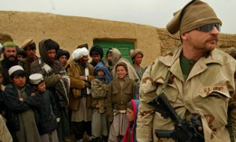 A U.S. Army Special Forces soldier is surrounded by a curious crowd of Afghan onlookers in a remote village in the mountains of western Afghanistan in 2002.