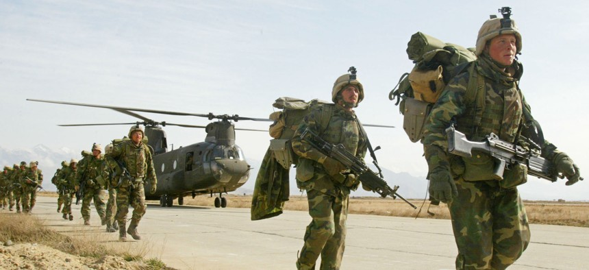 U.S. Army soldiers from the 10th Mountain and the 101st Airborne units disembark from a Chinook helicopter March 11, 2002 as they return to Bagram airbase from the fighting in eastern Afghanistan.