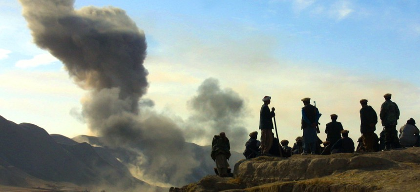 Northern Alliance soldiers watch as U.S. air strikes attack Taliban positions in Kunduz province, Afghanistan, Nov. 19, 2001.