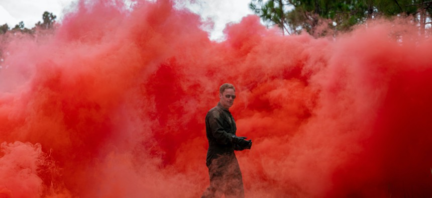 A U.S. Air Force pilot walks through smoke during Survival, Evasion, Resistance and Escape training at Poinsett Electric Combat Range in Wedgefield, South Carolina, Sept. 7, 2021.