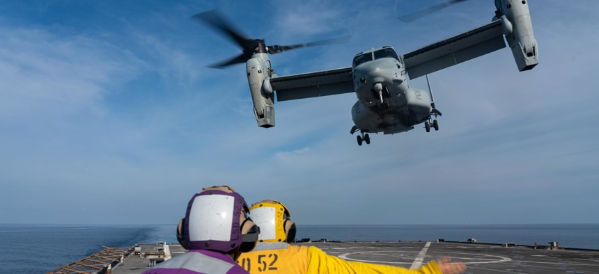 Boatswain's mate 2nd Class Thomas Schnell, right, from Omaha, Neb., and Culinary Specialist Seaman Daniel Francois, from Cap Haitian, Haiti, guide an MV-22B Osprey attached to Marine Medium Tilt-Rotor Squadron 165 (Reinforced), 11th Marine Expeditionary Unit, during flight operations aboard the amphibious dock landing ship USS Pearl Harbor, Sept 6, 2021.