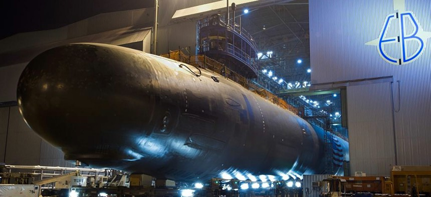 The Virginia-class attack submarine North Dakota (SSN 784) is rolled out of an indoor shipyard facility at General Dynamics Electric Boat in Groton, Connecticut.
