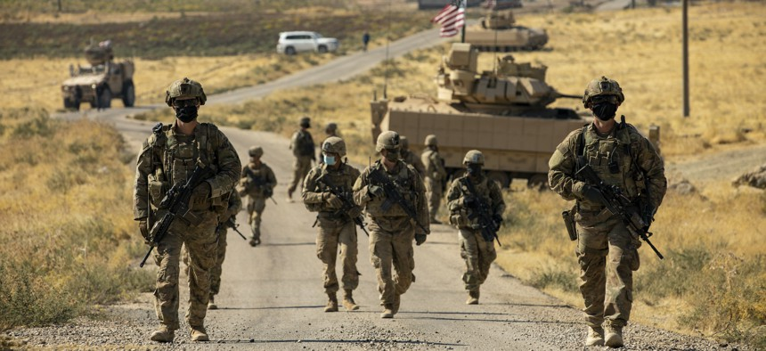 U.S. soldiers make their way to a oil production facility to meet with its management team, in Syria, Oct. 27, 2020.