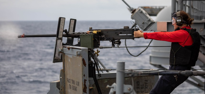 Aviation Ordnanceman Airman Mackinze Hallhanna fires a .50-caliber machine gun during a live-fire exercise aboard the Wasp-class amphibious assault ship USS Kearsarge, Sept. 21, 2021.