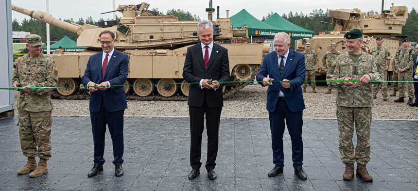 Lithuanian Minister of National Defense Arvydas Anušauskas, second from right, and Lt. Col. Paul Godson, commander of the U.S. Army's 3rd Battalion, 66th Armored Regiment, at a recent ribbon-cutting ceremony for Lithuania's Camp Herkus.