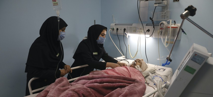Covid-19 patient Marhamat Asadi, who is in a medically induced coma, is tended by nurses Fatemeh Najmeh Sadeghi, left, and Fereshteh Babakhanlou at the COVID-19 ICU ward of Amir Al-Momenin hospital in the city of Qom, Iran, Sept. 15, 2021.
