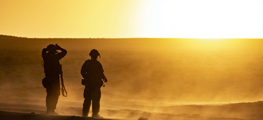 Two soldiers from 10th Special Forces Group Airborne look out over the desert of the National Training Center on Fort Irwin, California, Aug. 17, 2021.