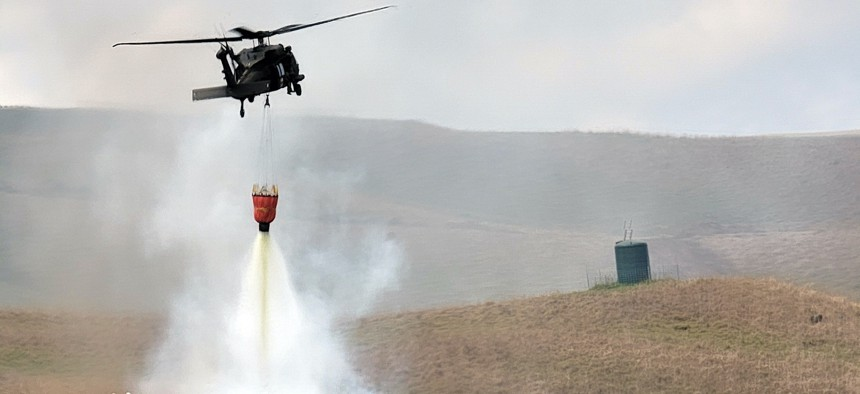 U.S. Army HH-60 Black Hawk pilots and flight crew assigned to Charlie Company, 3rd Battalion, 25th Aviation Regiment, 25th Combat Aviation Brigade, 25th Infantry Division, help local firefighters extinguish a fire using a Bambi bucket near the Pohakuloa Training Area, Hawaii, July 31, 2021.
