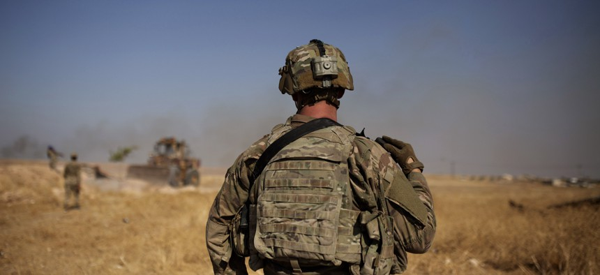 """In this Sept. 6, 2019, photo, a U.S. special forces soldier watches Syrian Kurdish soldiers dismantle a fortification in the so-called """"safe zone"""" on the border with Turkey near Tal Abyad, Syria."""