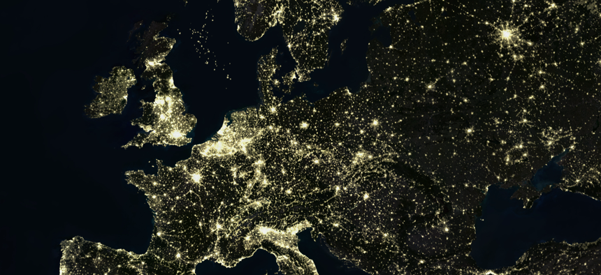 True colour satellite image of Europe at night with country borders.