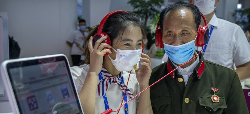 An attendant demonstrates a display for an elderly Chinese military veteran at a booth for Chinese telecom provider China Telecom at the PT Expo in Beijing, Sept. 28, 2021.