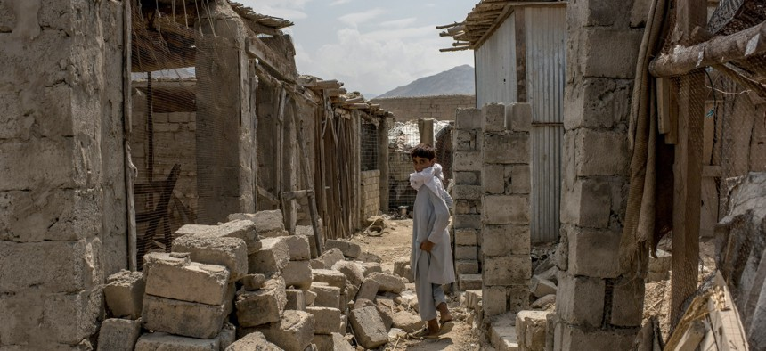 In this photo from July 2017, a boy walks through buildings damaged during fighting against the Islamic State of Iraq and Syria - Khorasan, or ISIS-K, in Nangarhar province, Afghanistan.