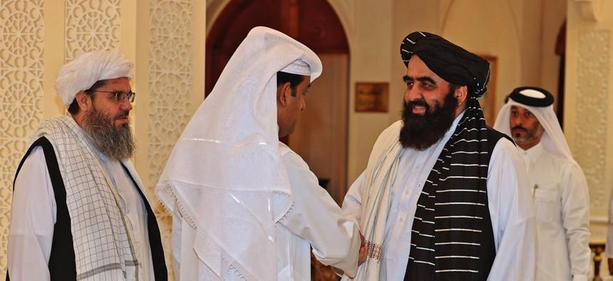 Qatar's envoy on counter-terrorism Mutlaq al-Qahtani, left, shakes hands with Taliban co-founder Mullah Abdul Ghani Baradar in Qatar's capital Doha, on October 12, 2021.