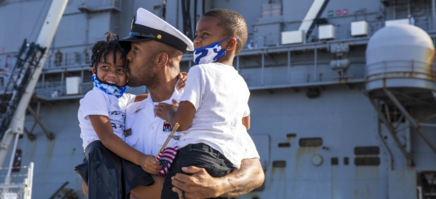 Chief Personnel Specialist Patrick Pean, assigned to the USS Iwo Jima, embraces his children after returning from deployment on Oct, 11, 2021, at Naval Station Mayport, Fla.