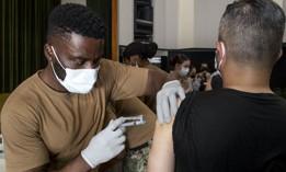 Navy Seaman Valentine Anebere, a hospital corpsman assigned to U.S. Naval Hospital Yokosuka Branch Health Clinic Sasebo, administers doses of the Moderna COVID-19 vaccine to an employee at Commander Fleet Activities Sasebo, Japan, July 28, 2021.