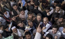 People gather outside a government passport office recently re-opened after Taliban announced they would be issuing a backlog of applications approved by the previous administration in Kabul, Afghanistan, Oct. 6, 2021.