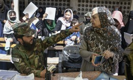 A Taliban fighter talks with an elderly woman at the government passport office which re-opened after the Taliban announced they would be issuing a backlog of applications approved by the previous administration in Kabul, Afghanistan, Oct. 17, 2021.