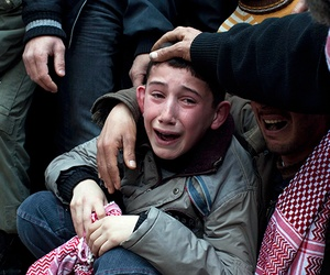 A Syrian child mourning at the funeral of his father