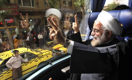 Newly elected Iranian President Hasan Rouhani waves from his campaign bus.