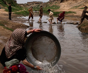 Girls in Pakistan washing their laundry near a polluted stream