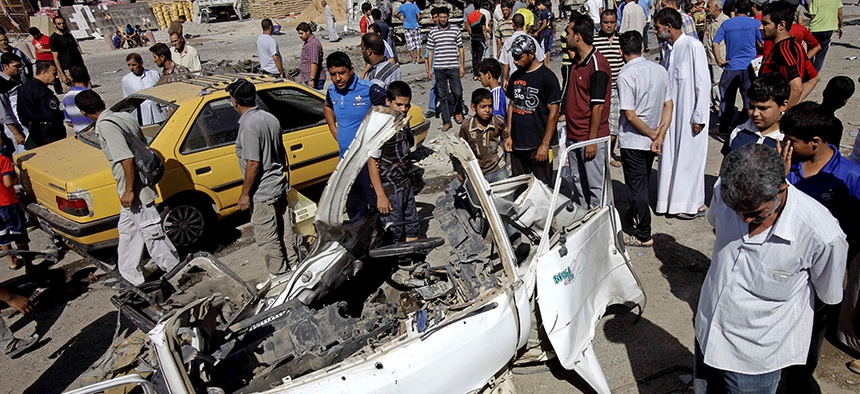 Iraqis walk around the aftermath of a car bomb attack in Sadr City, Baghdad