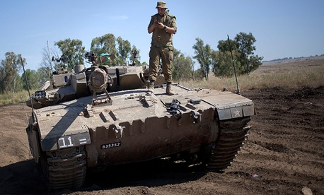 An Israeli soldier on top of a tank in the Golan Heights