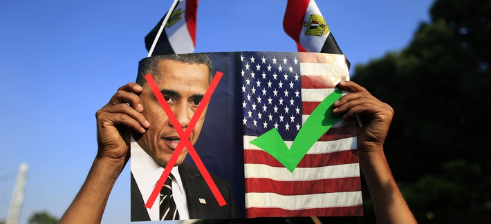 A protestor holds up a photo of President Obama and a U.S. flag in Cairo, Egypt