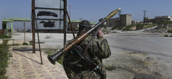 A Syrian rebel holds a rocket propelled grenade at a key highway
